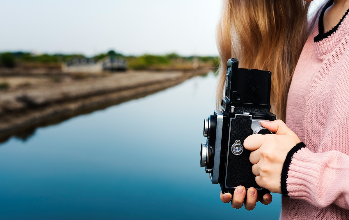 Girl using a vintage camera outdoors