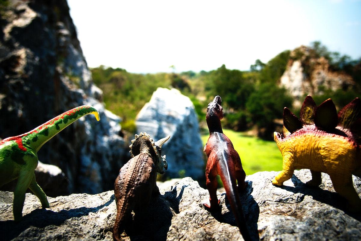 Group of dinosaur toys on a rock