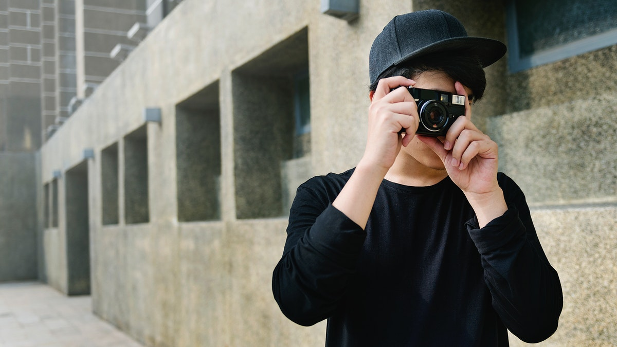 Young guy taking photos outdoors