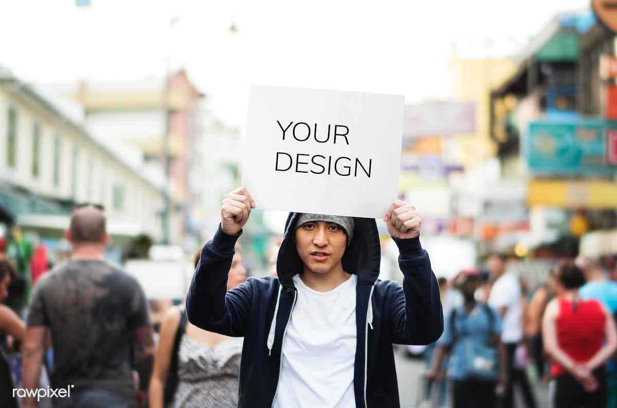 8d575d0a92c4d Young asian man holding empty placard outdoors