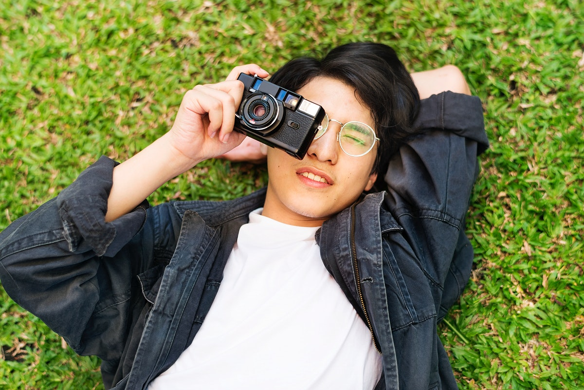 Young asian boy taking a photo while lying on the grass