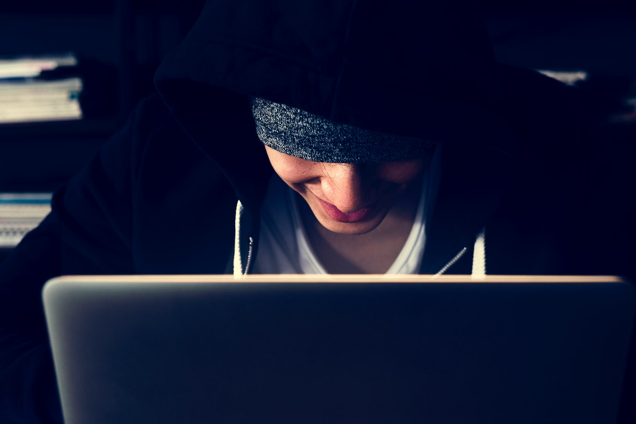 Hacker In Hoodie Using Laptop For Cyber Crime Royalty Free Photo 39409