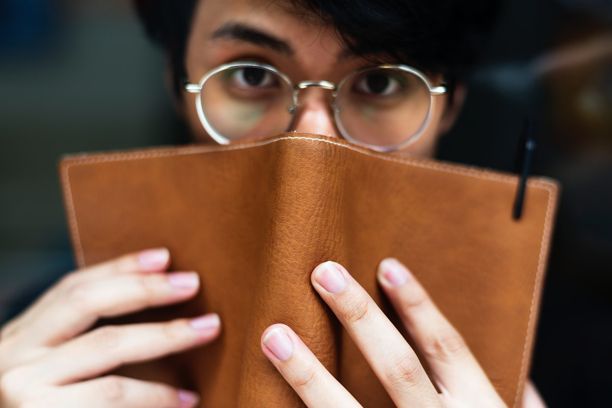 Young asian man using leather book to cover his face
