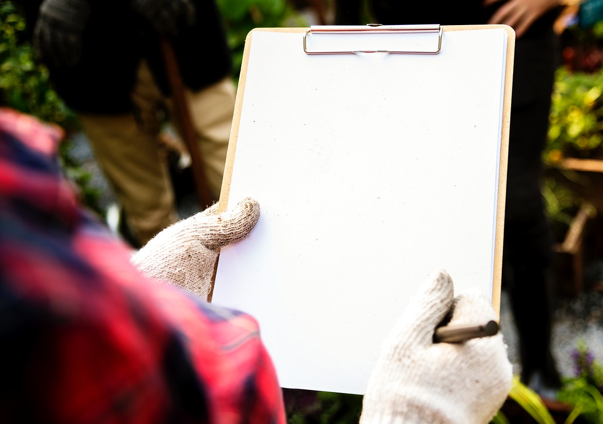 Woman checking list on clipboard for organic fresh agricultural product