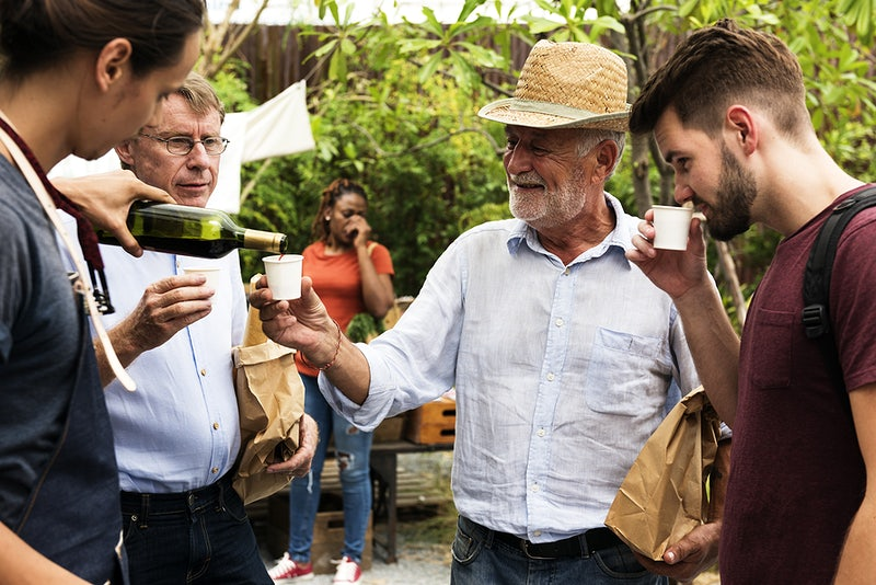 Man Offering Red Wine to Customer at Food Stall