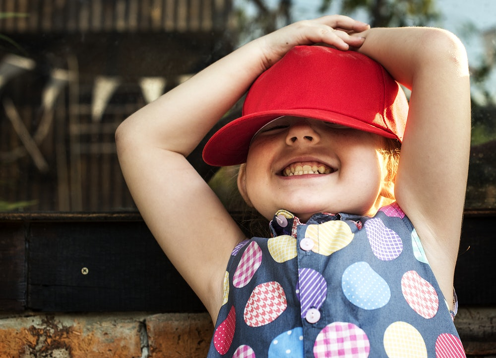 Girl is smiling with red cap