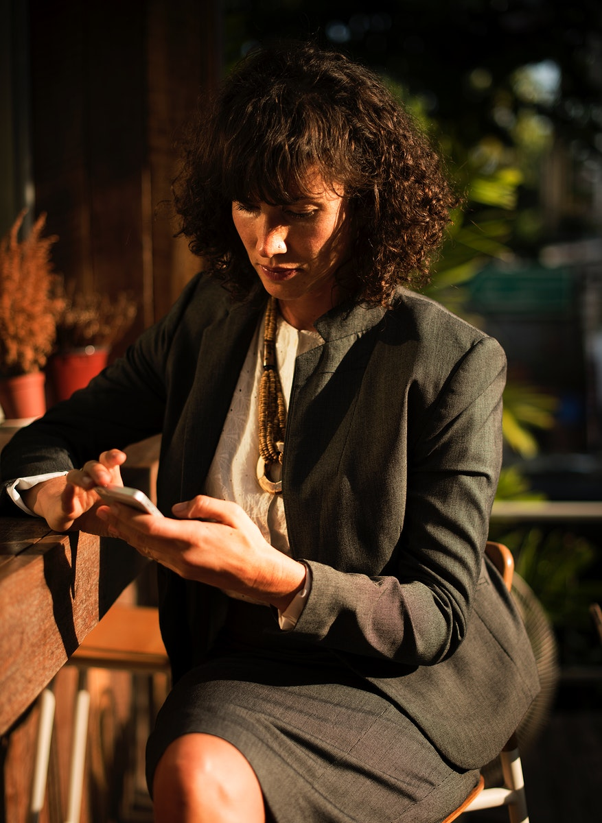 Businesswoman using mobile phone in coffee shop