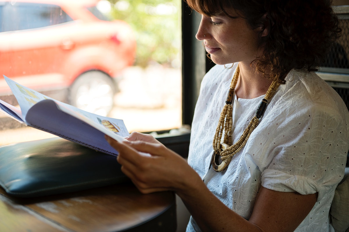 Woman reading magazine at coffee shop