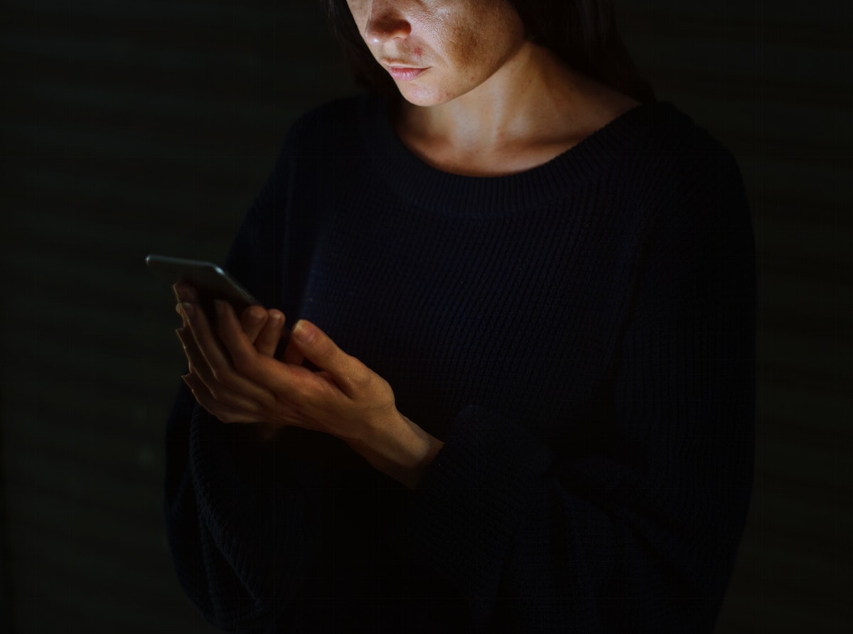 Woman Using Mobile Phone in the Dark