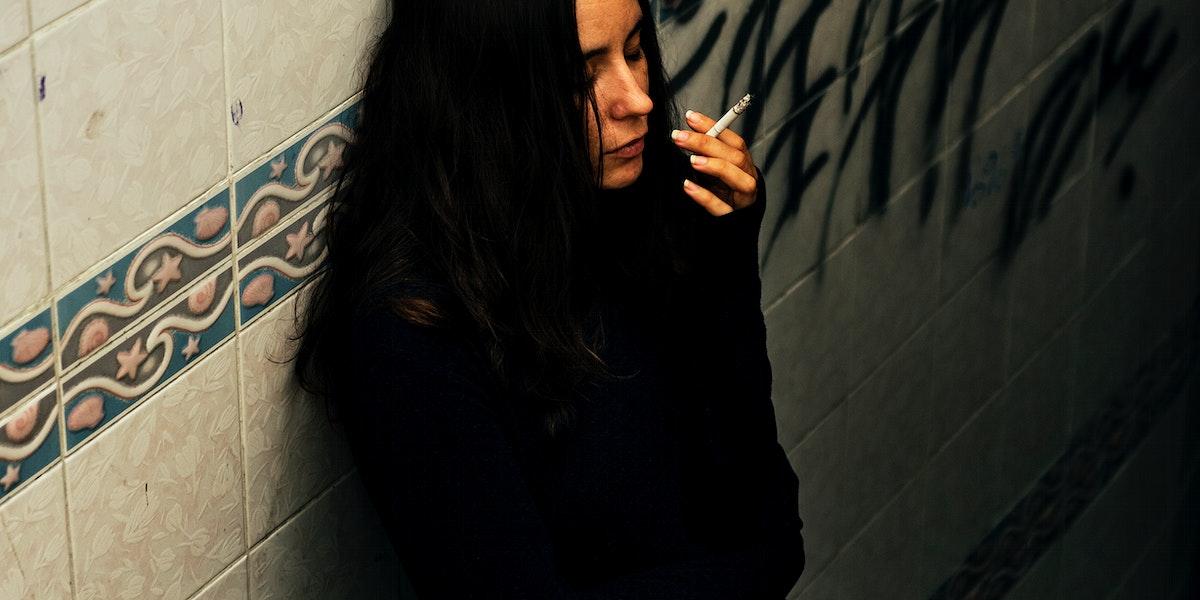 Woman smoking cigarette alone
