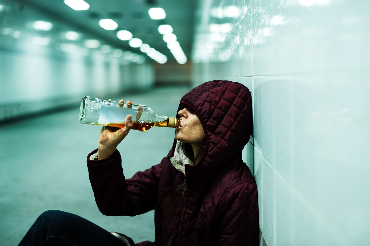 Homeless Alcoholic Drinking Alcohol Sitting on The Floor