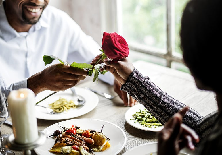 Romantic Man Giving a Rose to Woman on a Date