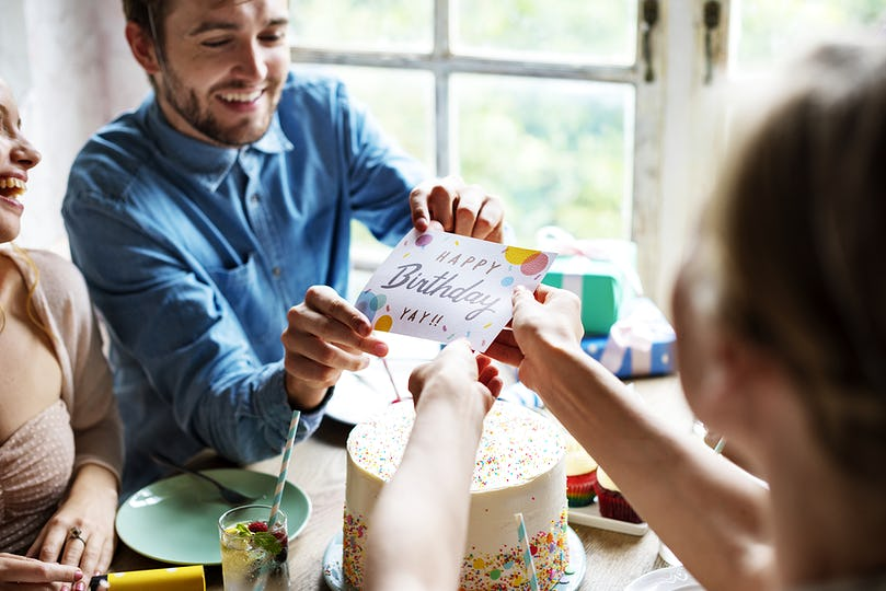 Man Giving Birthday Wishing Card to Friend