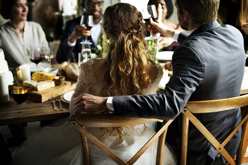 Bride and Groom Having Meal with Friends at a Wedding Reception