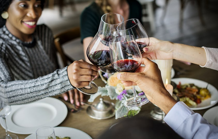 People Clinging Wine Glasses Together in Restaurant