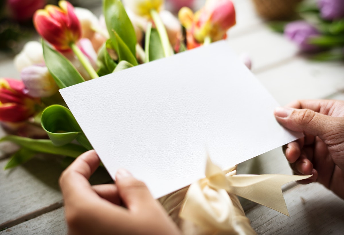 Hands Holding Design Space Empty Card with Tulips Flowers as Background