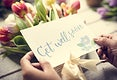 Hands HoldingGet Well Soon Wishing Card with Tulips Flowers as Background