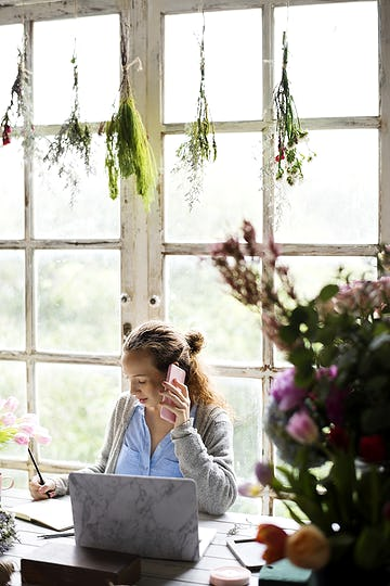 Woman talking on the phone with plants hanging above