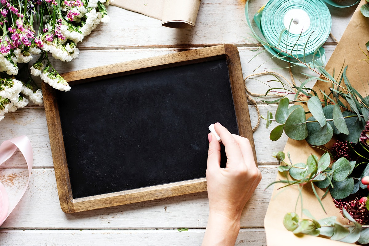 Hand Holding Chalk Write on Blank Design Space Black Board with Flowers Decorate