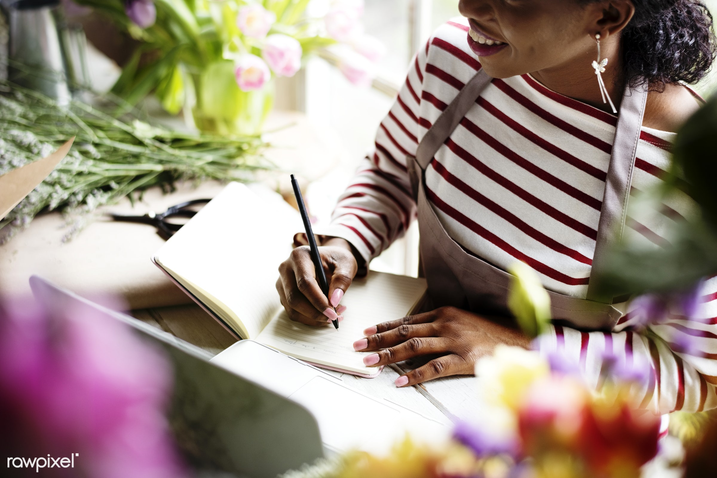 Black person writing on a notebook - black, writing, closeup, notebook, pencil, florist, workspace, laptop, desk, table,...