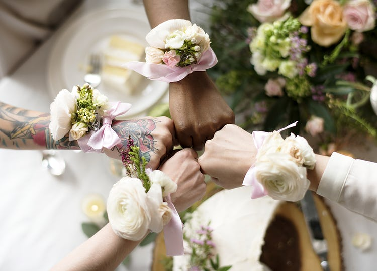 Bridesmaids party hands with corsage fists together