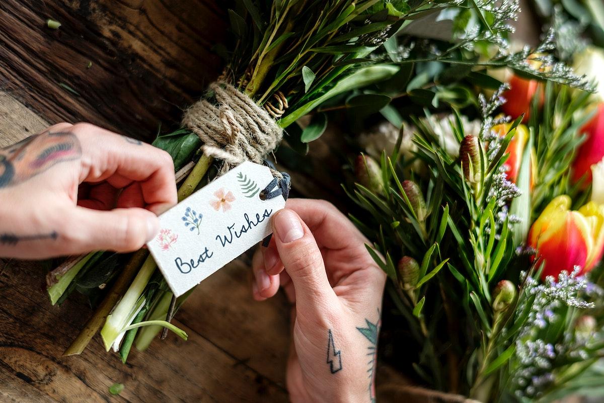 Florist Making Fresh Flowers Arrangement Bouquet with Best Wish Tag