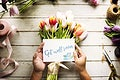 Hand Holding Show Get Well Soon Card with Tuips Flowers Background