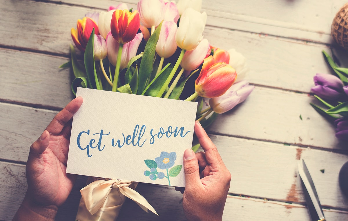 Hand Holding Show Get Well Soon Card with Tuips Flowers Backgrou