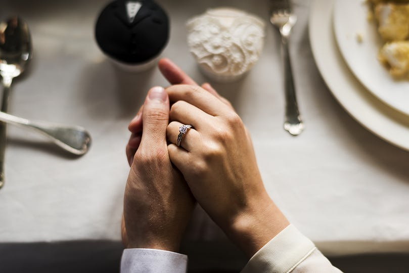 Close up of wedding couple hands holding each other