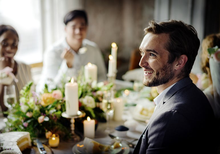 Groom listening to a speech at a wedding reception table