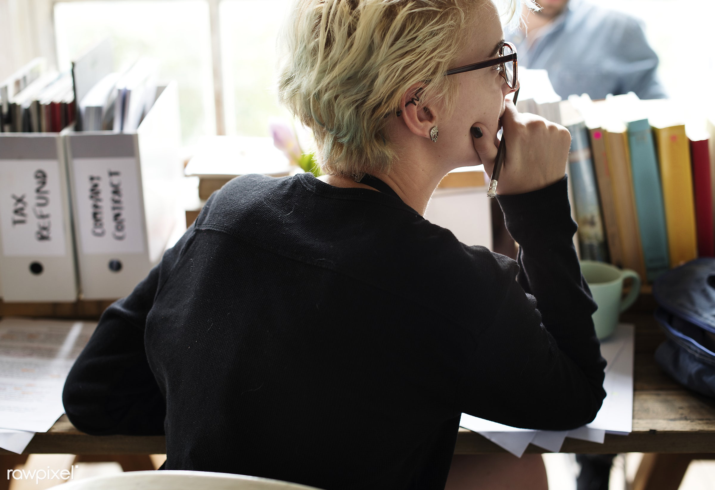 Blonde woman contemplating at her desk - woman, thoughtful, attach, alone, attached, blonde, brainstorming, desk, gesture,...