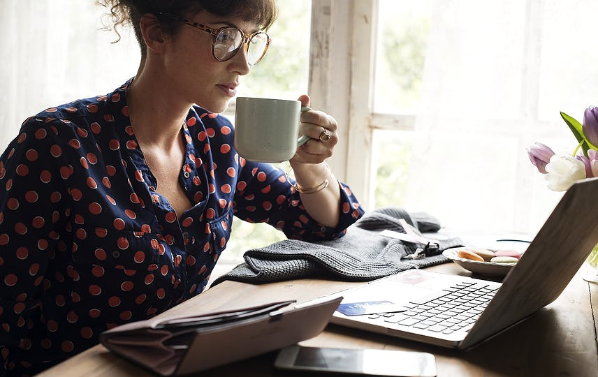 Woman Hands Holding Coffee Cup Working on Laptop