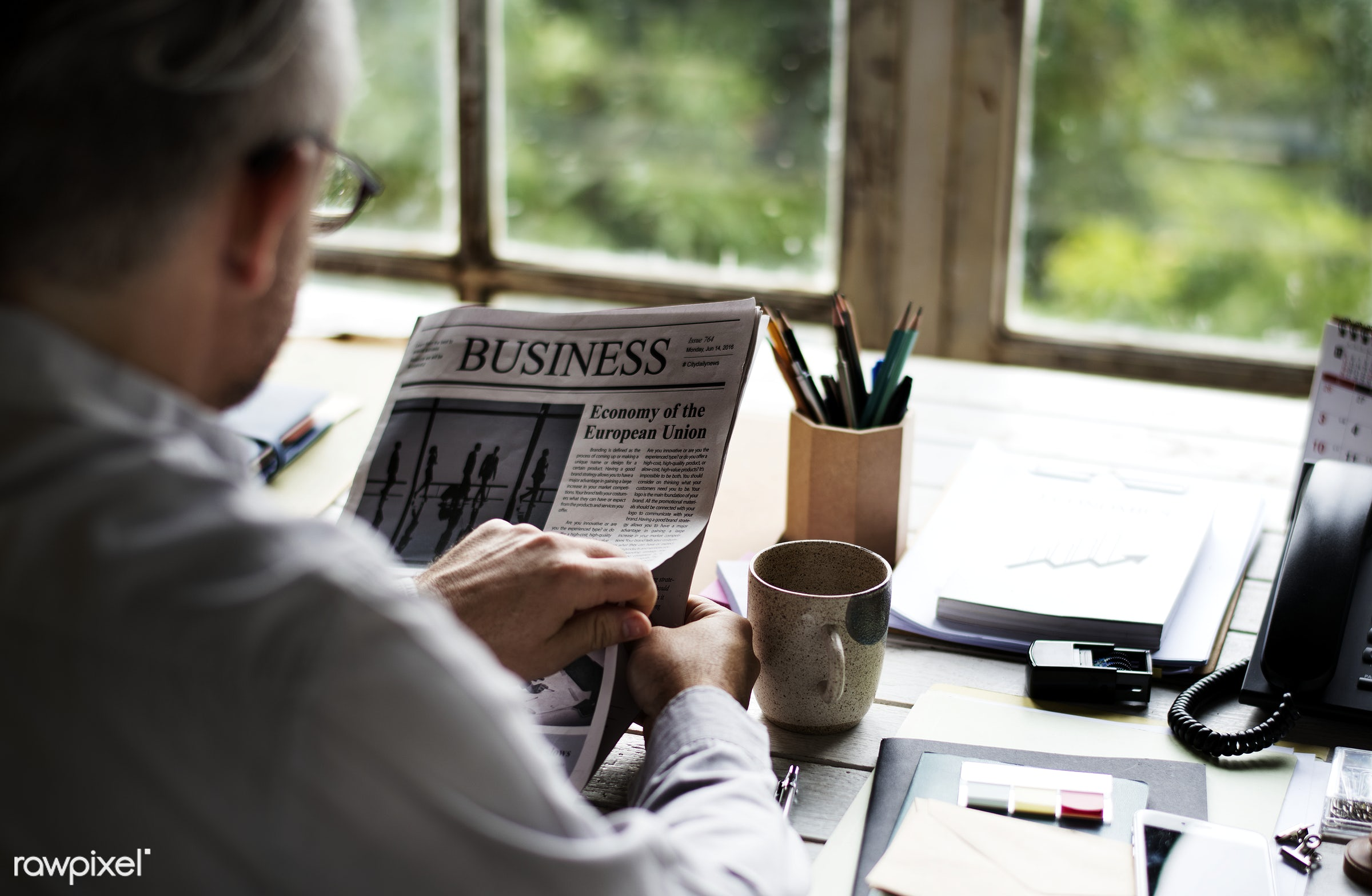 Man reading a newspaper at his desk - news, attach, attached, coffee, current events, leisure, morning, newspaper, person,...
