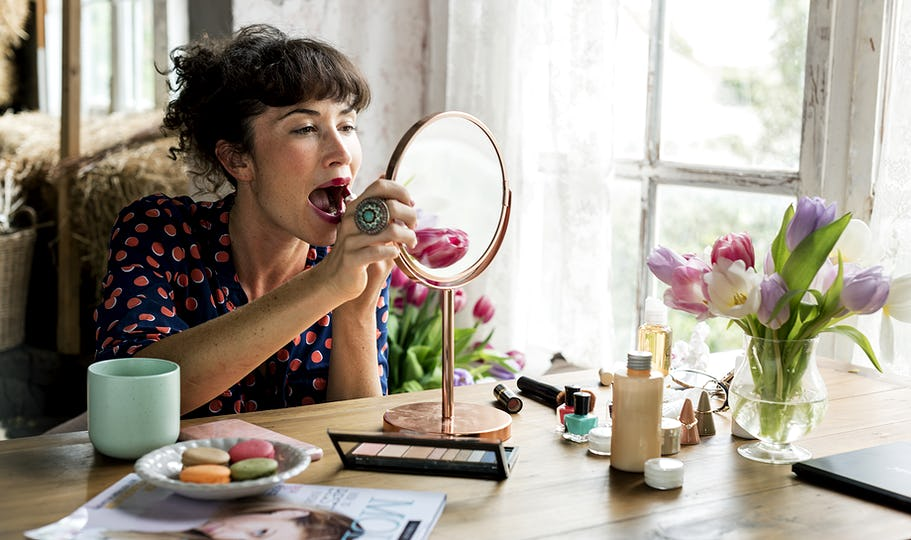Woman putting on lipstick with a mirror