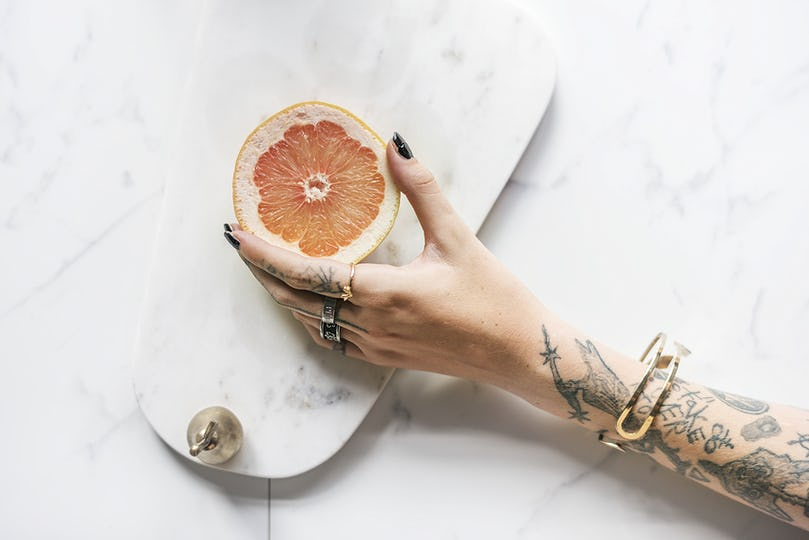 Tattooed woman holding an orange over a marble background
