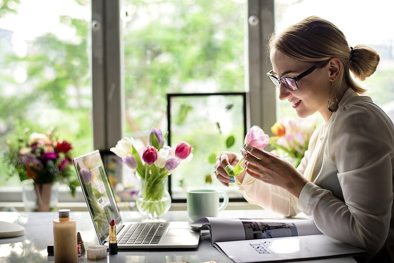 Woman smelling a flower in the office
