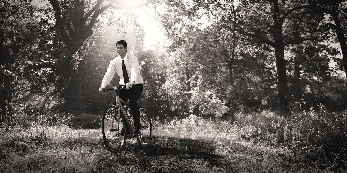 Businessman biking through a forest