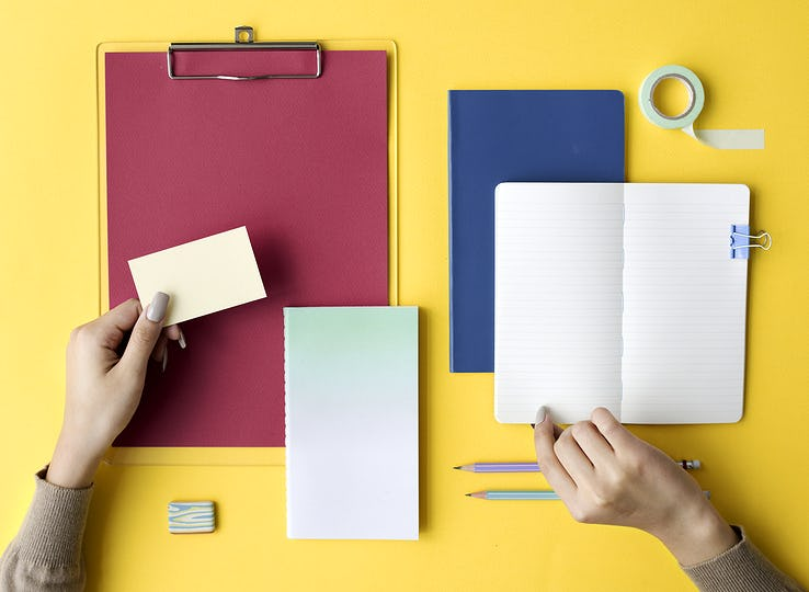 Hand Open Blank Notebook and Stationery on Yellow Background