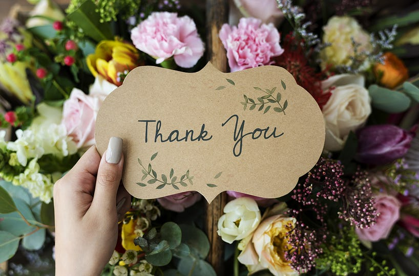 People Hand Holding Thank You Card with Flowers Bouquet Background