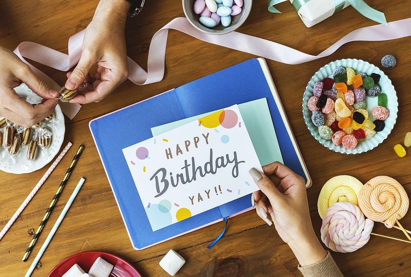 Hand Holding Birthday Wish Card on Wooden Table Background with Sweet Snacks