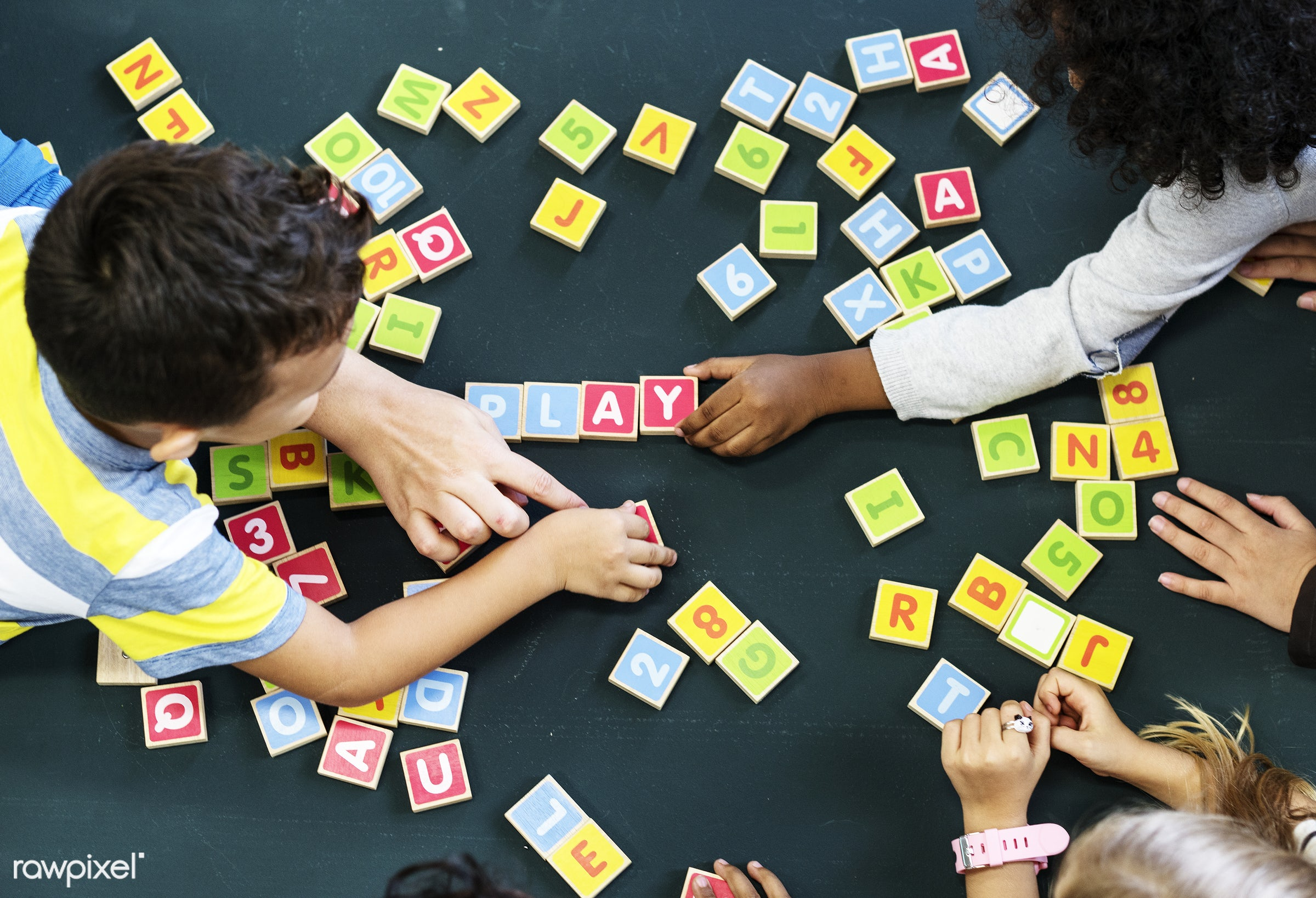 Kids spelling out words with alphabet blocks - aerial, alphabets, black table, childhood, children, education, elementary,...