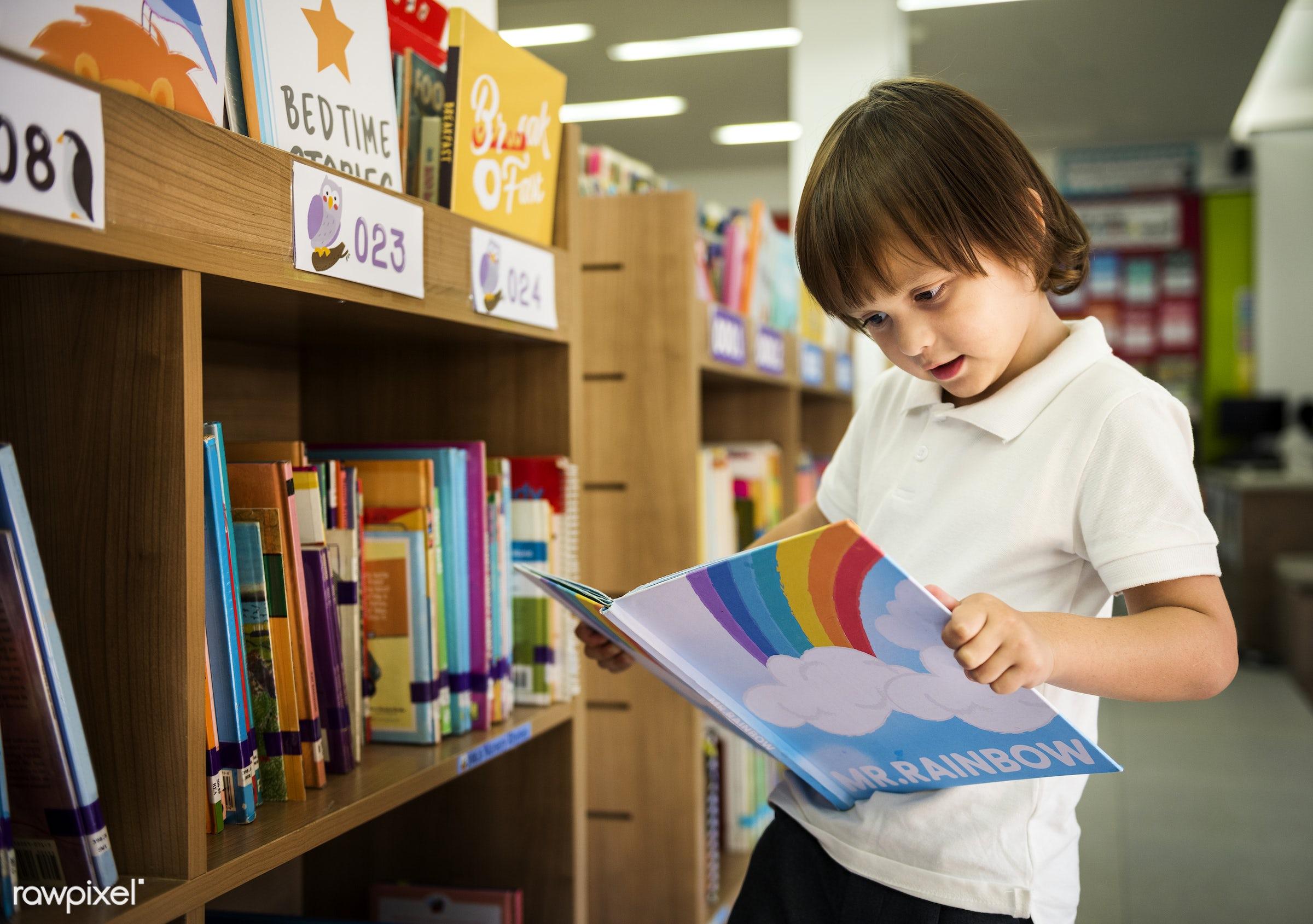 Boy reading book at a school library - library, bookshelf, school, alone, asian, books, boys, children, education,...