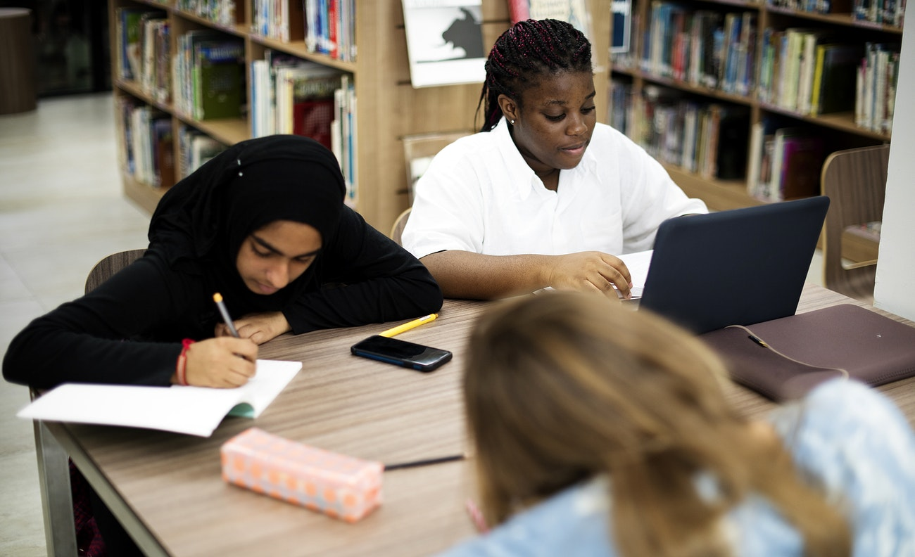 Diverse group of high school student studying doing homework in library