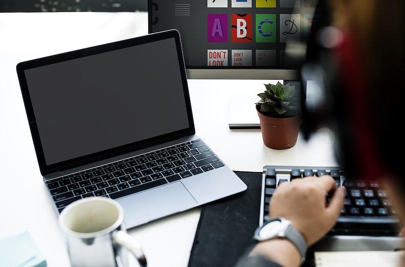 Laptop Screen Showing Black Desktop on Whtie Table beside Working Man