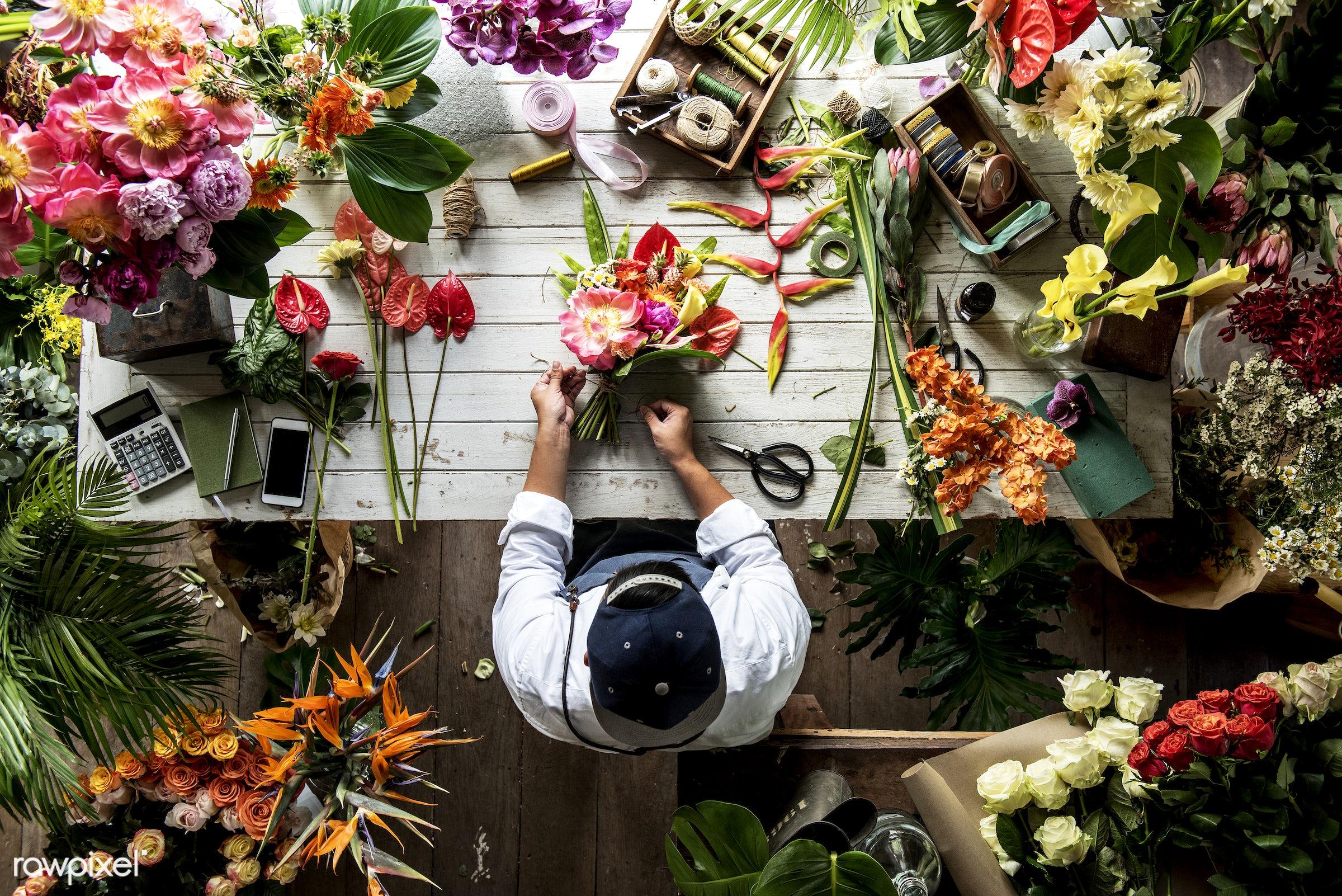 Florist making a flower arrangement in a flower shop - bouquet, person, store, small business, indoors, self-employed,...