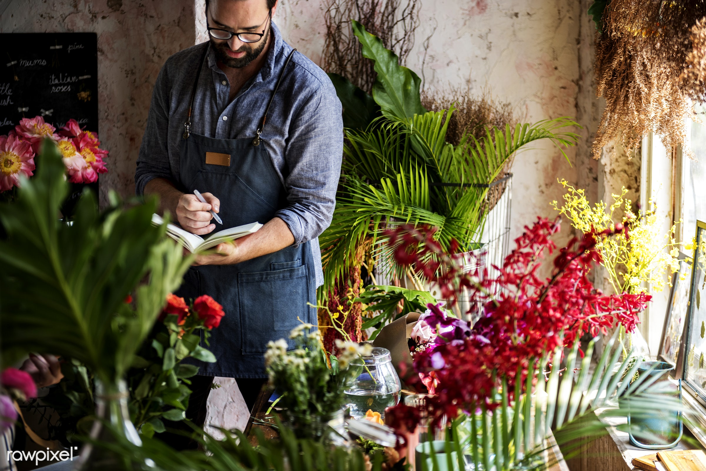 Man taking notes in a flower shop - apron, arrangement, beard, beautiful, bouquet, bunch, business, candid, casual, colorful...