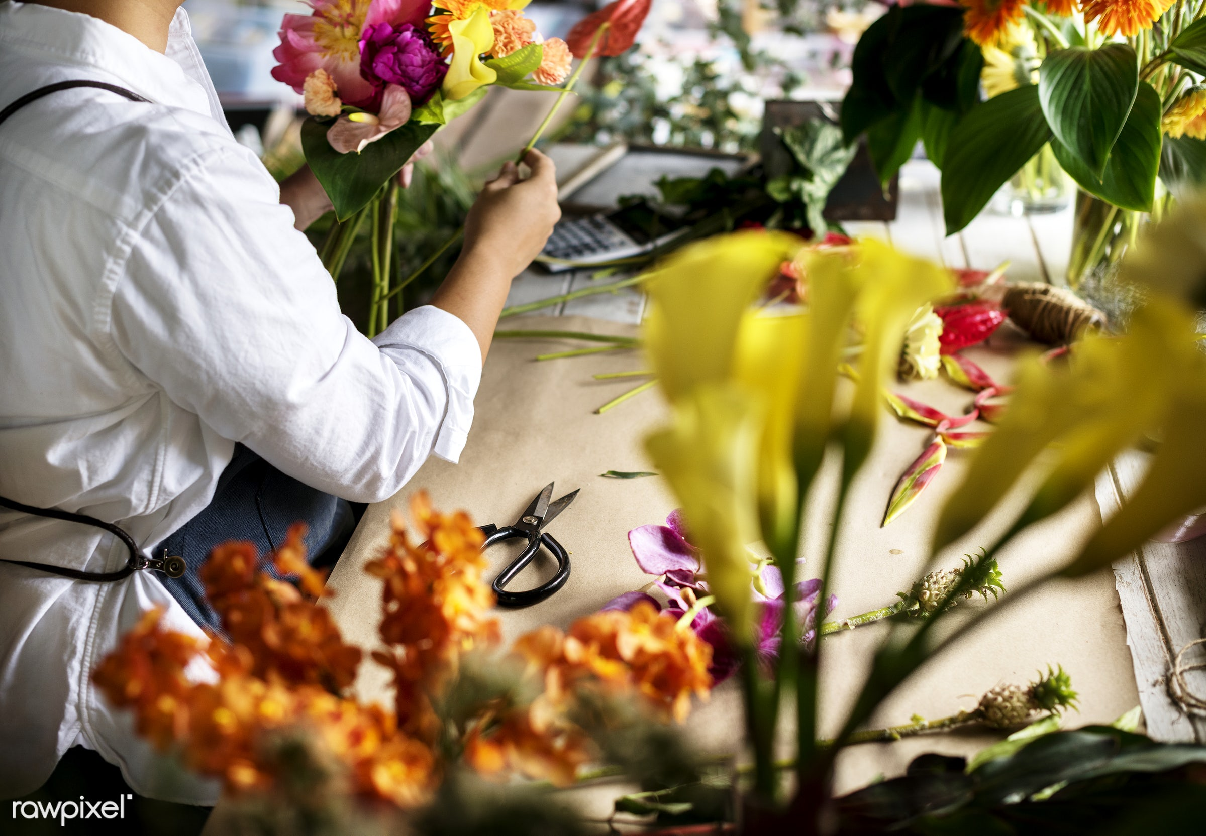 Florist making a flower arrangement in a flower shop - bouquet, person, store, small business, indoors, self-employed,...