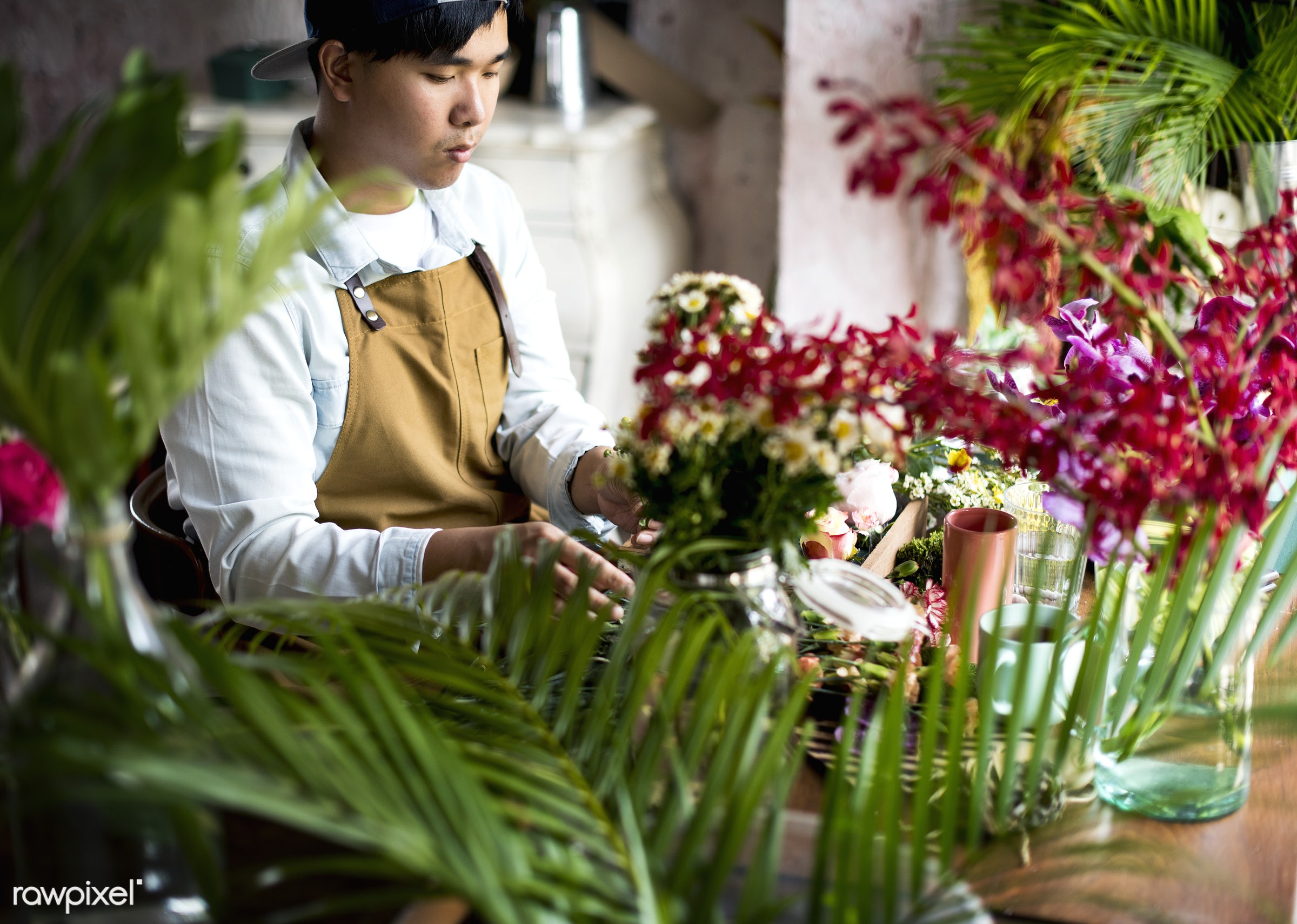 Florist making a flower arrangement in a flower shop - bouquet, person, store, indoors, self-employed, business, asian,...