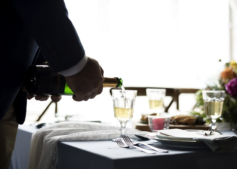 Hand Pouring Filling Champagne Drink to Glasses