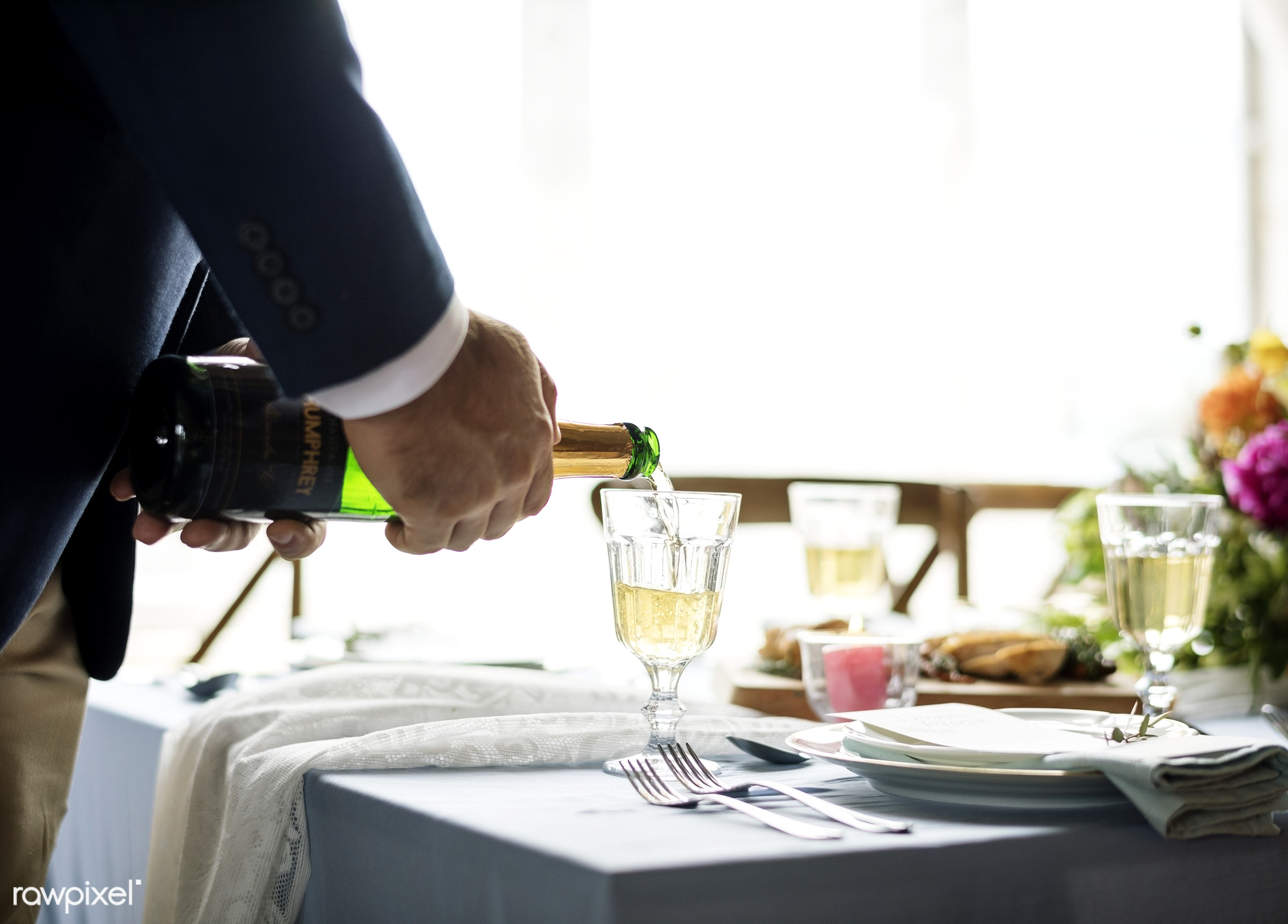 Hand pouring champagne in a glass - wine, drink, alcohol, bottle, hand, closeup, table, glass, pouring, setting, plate,...